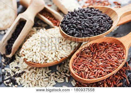 Collection of exclusive gourmet rice in wooden spoons - brown rice red rice black rice close up
