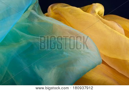 Combination of green and yellow transparent organza fabric lay in form of waves