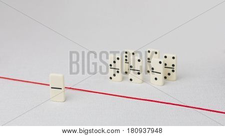 Expelled from the group, unable to cross the red line that separates them. Scene with group of domino. Concept of accusation guilty person, bulling or outcast in the team. Bright background.