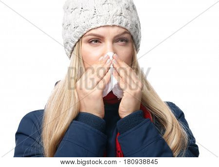 Young woman using tissue to blow her nose on white background