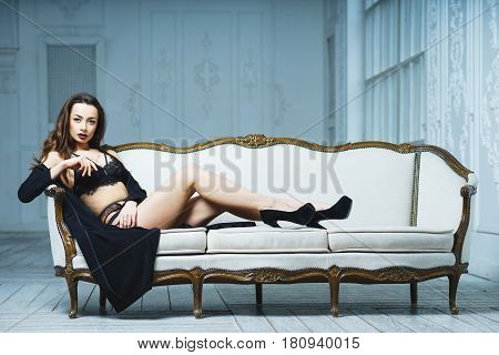 Young attractive girl in black lace lingerie lies on a white sofa and looks directly at the camera. Boudoir. Model in a black dress posing for a photographer. Soft focus.