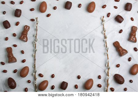 Chocolate Easter Eggs, Rabbits, Casks, Green Sweets On Concrete Background