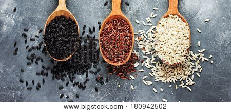 Collection of exclusive gourmet rice in wooden spoons - brown rice red rice black rice