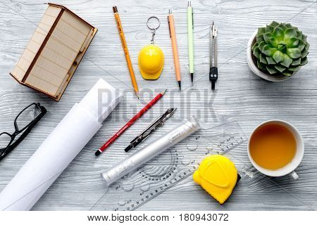profession concept with architect desk and constructor tools and cup on light wooden background top view