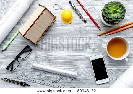 architect office with tools, cup and mobile in profession concept on light wooden desk background top view mock up