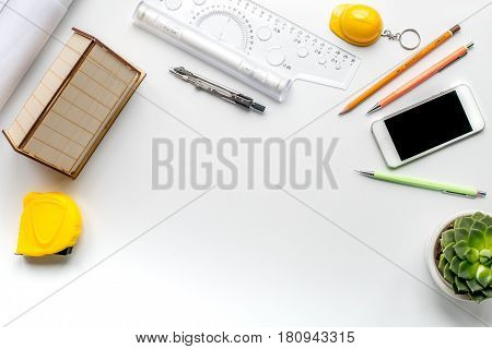 profession concept with architect desk and constructor tools with phone on white background top view mock-up