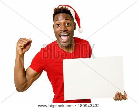 young attractive black afro american man in Christmas Santa hat smiling happy and showing blank billboard with copy space for adding xmas advertising text isolated on white in sales and offer concept