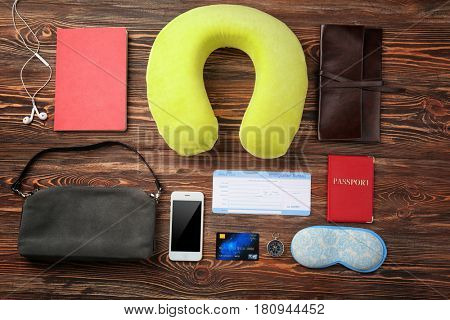 Travel pillow and things for traveling on wooden background