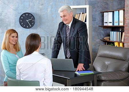 Young woman and daughter meeting with teacher at school