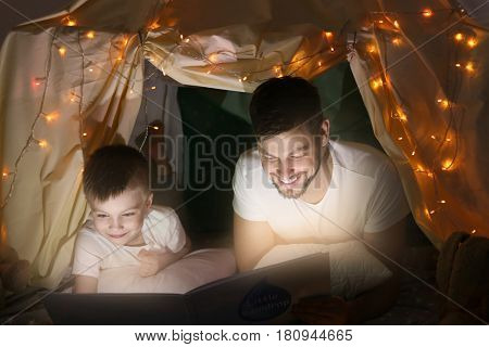 Father and son reading book in hovel at home