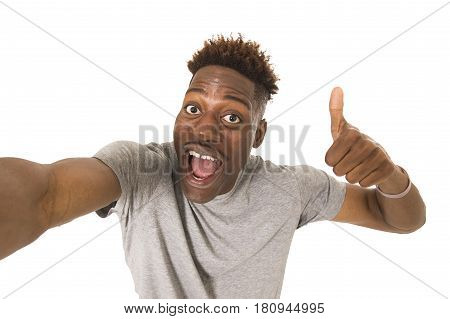 young afro american man smiling happy taking selfie self portrait picture with mobile phone looking excited having fun posing cool isolated in white background in communication technology concept