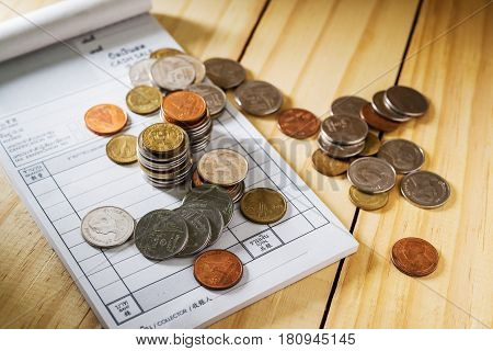 Save money concept Stack of coins with utility bill on wooden table