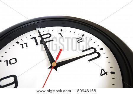 Fragment of big round wall clock with a black rim isolated on white background close-up and arrows showing three o'clock close-up