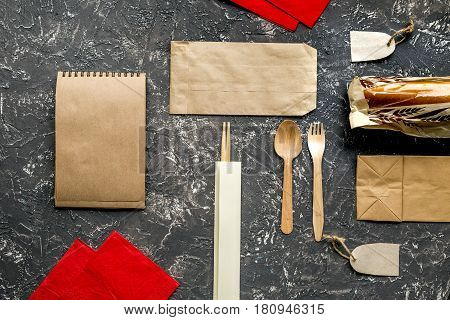 food delivery service workdesk with paper bags, flatware and sandwich on gray background top view mockup