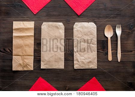 food delivery service workdesk with paper bags and flatware on wooden background top view mockup