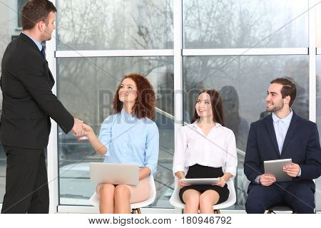 Job interview concept. Manager shaking woman's hand in office hall