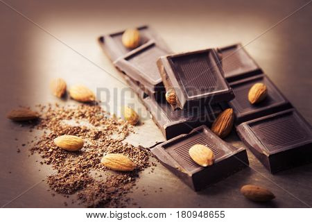 The broken pieces of nut chocolate. Grated chocolate on a brown background