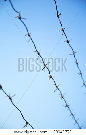 Barbed wire fence on  the blue sky. Blured edges