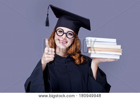 Photo Of Beautiful Young Alumnus With Pile Of Books On The Wonderful Grey Studio Background