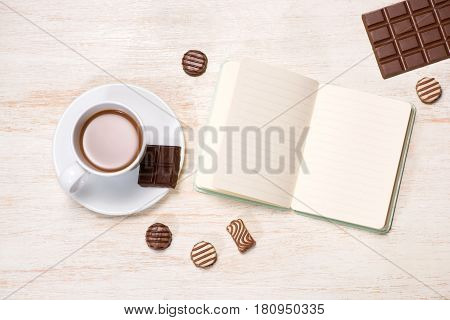 Coffee milk cup and delicious chocolates with notebook on table.