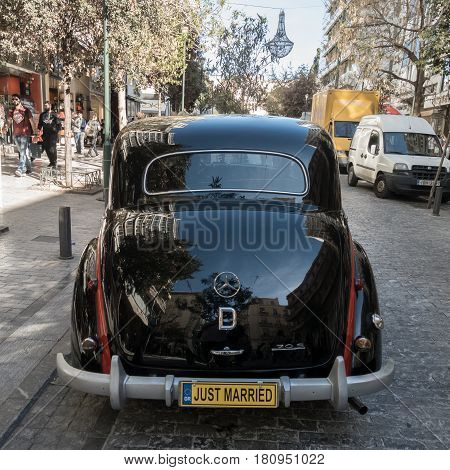 Athens Greece - 23 March 2017: Rear of Black Antique Mercees-Benz 170 S car parked on Ermou Street for use as a wedding limousine. The Mercedes-Benz 170 S was a luxury passenger car manufactured between 1949-1955.