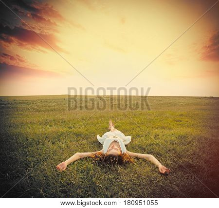 Photo Of Beautiful Young Woman Lying In The Field On The Sky Background