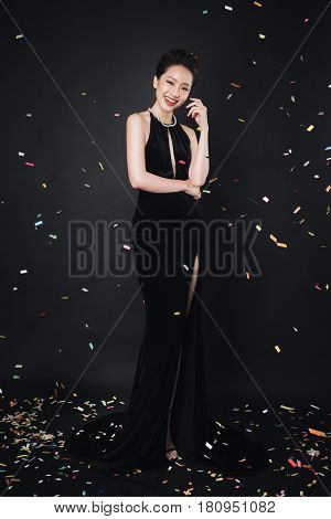 Asian Woman With Fashion Makeup In Luxury Black Dress While Confetti Falling On Her.