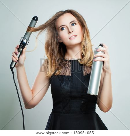 Glamorous Woman with Blonde Wavy Hair Ironing It Using Curling Iron. Happy Girl With Gorgeous Healthy Smooth Hair Using Curler For Perfect Curls. Hairstyle And Hairdressing