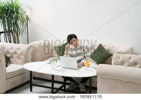 Asian Young Businessman Working On His Laptop In A Coffee Shop
