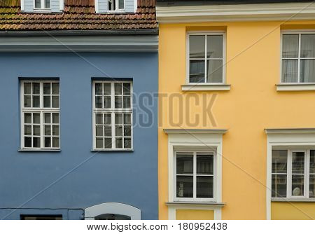 Two neighboring old houses. The houses are painted in yellow and blue colors. City of Riga. Latvia.