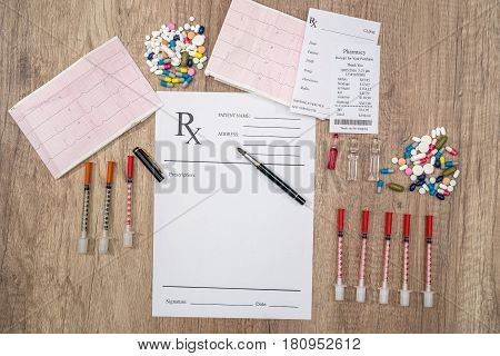 rx blank with pills syringe and pharmacy receipt on desk.