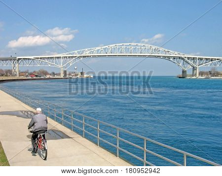 The Blue Water Bridge joins international neighbors Port Huron, Michigan, USA (left) and Sarnia, Ontario, Canada (right). Lake Huron flows under the two spans of the bridge and into the St. Clair River, near where a man can be seen riding his bicycle.