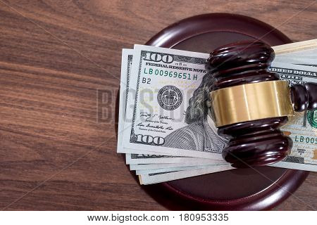 Us Money with judges hammer on wooden table top view.