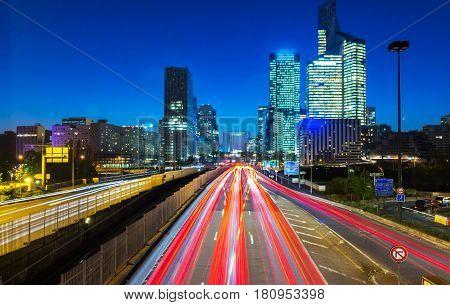 Night multi-lane road with skyscrapers of the La Defense Paris France. Long exposure