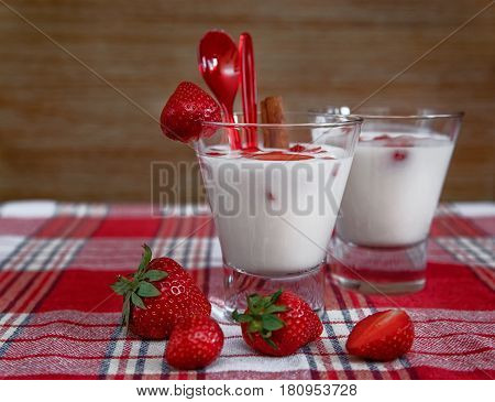 Two Glasses of Milk Cocktail,Red Fresh Strawberries with Plastic Spoons on the Check Tablecloth.Breakfast Organic Healthy Tasty Food.