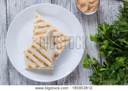 shawarma in thin pita bread with chicken and vegetables on a white plate