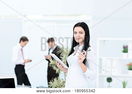 Happy businesswoman with colleagues in the background in modern office