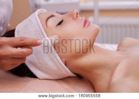 The doctor-cosmetologist makes the procedure vacuum face cleaning of a beautiful young woman in a beauty salon.Cosmetology and professional skin care.