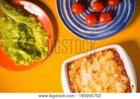 Lasagna, tomatoes, green salad on a yellow background horizontal