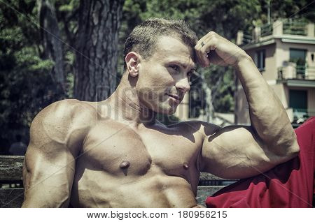 Handsome Muscular Shirtless Hunk Man Outdoor at Seaside Looking at Camera, Sitting on Bench under the Sun