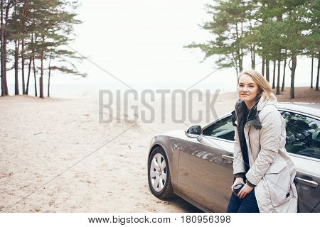 Happy woman next to car, relaxing on road trip adventure travel and drinking hot cup of take-away coffee. Resting after having long distance car trip, parking with car near the seashore, far away from the city.