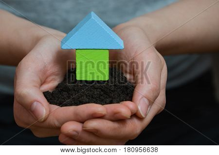 Female hands holding a piece of land with wooden house