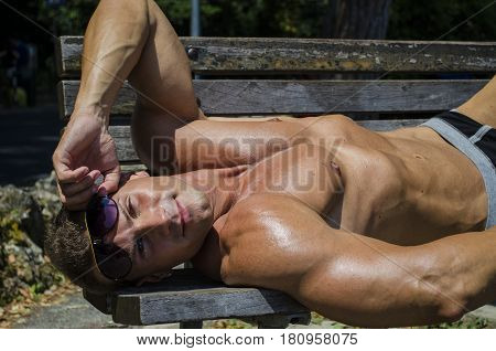 Handsome Muscular Shirtless Hunk Man Outdoor at Seaside Looking at Camera, Layihg on Bench under the Sun