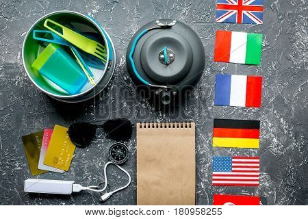 Preparation for traveling with loudspeaker, flags and sunglasses on gray desk background top view