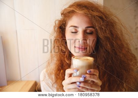 Close up portrait of a pretty young woman smelling her coffee drink aroma in a glass cup with eyes closed