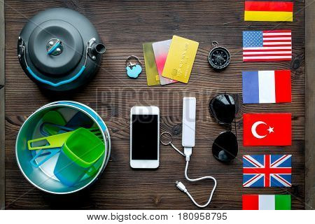 Preparation for traveling with cards, flags and mobile on wooden desk background top view