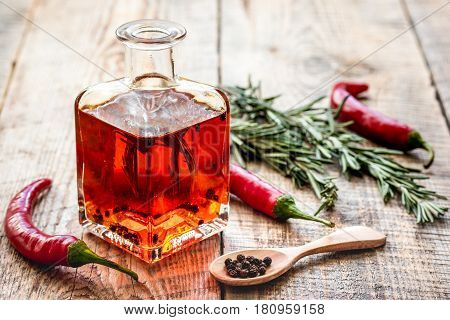 extra oil in carafe with spices and fresh chili on wooden desk background