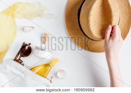 Sun protection cosmetic cream and lotion with beach outfit, sunglasses and hat on white background top view