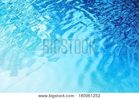 Photo of a blue bright water texture in a river with sun glares