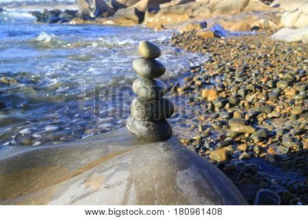 Amazing stack of stones on green moss at seaside beach group of pebble balance on large rock as meditation concept for Zen or strong mind or teamwork spirit